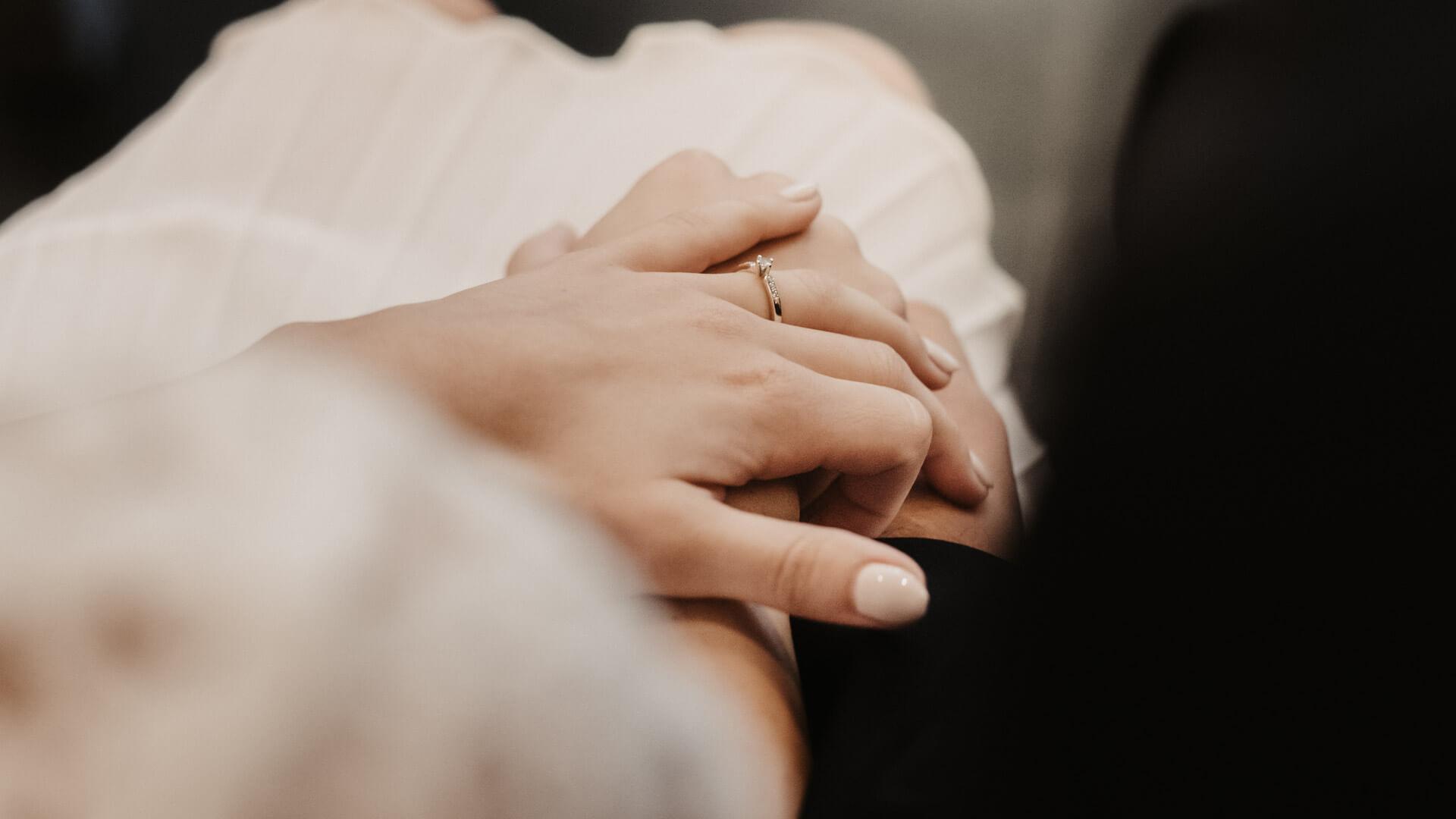 Brautpaar hält sich kurz vor der Trauung die Hände.