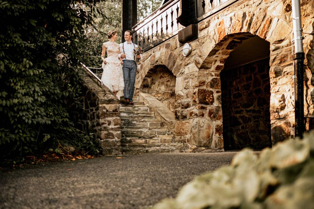 Brautpaar geht gemeinsam eine Treppe herunter und schaut sich in die Augen