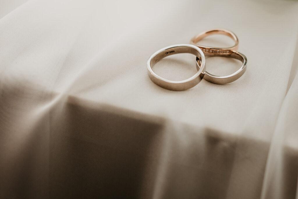 Trauringe eines Brautpaares auf seidenem Tuch